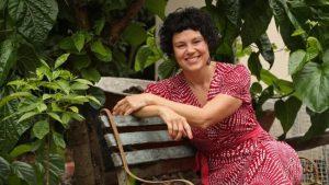 Author Josie Dietrich sitting on a bench in her garden